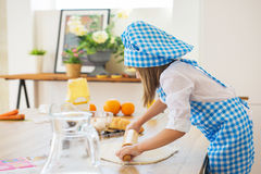 Little girl in a cook clothes rolls a circle of dough on a table Stock Image