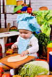 Little girl in a cook clothes rolls circle of dough on table Royalty Free Stock Image