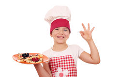 Little girl cook with crepes and ok hand sign Royalty Free Stock Images