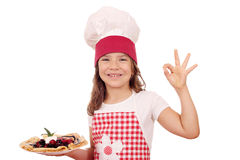 Little girl cook with crepes and ok hand sign Royalty Free Stock Photography