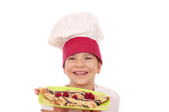 Little girl cook with crepes on plate Royalty Free Stock Images