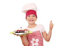 Little girl cook with crepes on plate and thumb up Stock Photo