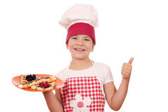 Little girl cook with crepes and thumb up Stock Photos