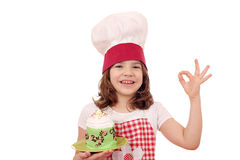 Little girl cook with cupcake and ok hand sign Stock Image