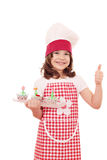 Little girl cook with cupcakes and thumb up Royalty Free Stock Photos