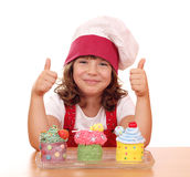 Little girl cook with cupcakes and thumbs up Royalty Free Stock Photography