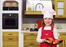 Little girl cook with delicious chicken drumstick in kitch Stock Images