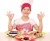 Little girl cook with delicious crepes on table and ok han Stock Photos