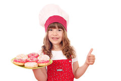 Little girl cook with donuts and thumb up Stock Images