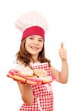 Little girl cook with donuts and thumb up Royalty Free Stock Image