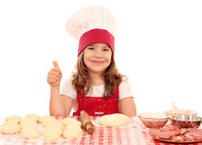 Little girl cook with dough and thumb up Stock Photo