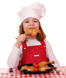 Little girl cook eat chicken drumstick Stock Images