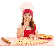 Little girl cook eat roll Stock Images
