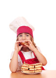 Little girl cook eating apple cake Stock Image