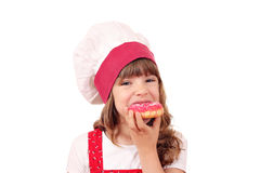Little girl cook eating donuts Stock Image