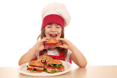 Little girl cook eating sandwich Royalty Free Stock Photos