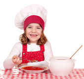 Little girl cook eating soup Royalty Free Stock Photos