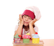 Little girl cook enjoying cupcakes Stock Photography