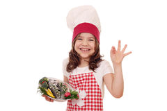 Little girl cook with fish and ok hand sign Stock Photography