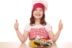 Little girl cook with fish and thumbs up Stock Images