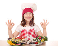 Little girl cook with fishes and ok hand sign Royalty Free Stock Photos