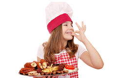 Little girl cook with grilled meat and ok hand sign Royalty Free Stock Photo