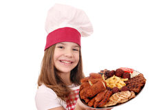Little girl cook with grilled meat and salad on plate Stock Photography