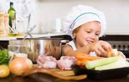 Little girl in cook hat cooking soup Stock Photography