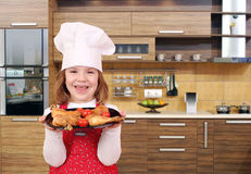 Little girl cook hold dish with chicken drumstick in kitch Stock Photos