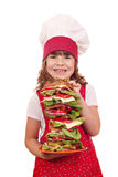 Little girl cook hold dish with tall sandwich Stock Image