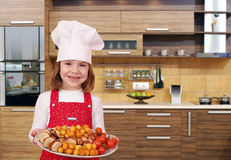 Little girl cook hold plate with gourmet food in kitchen Stock Photo