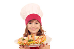 Little girl cook hold plate with salmon seafood Stock Photos