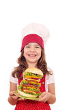 Little girl cook holding a big hamburger Stock Photos