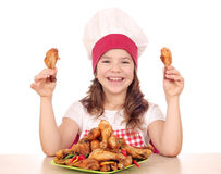 Little girl cook holding chicken drumsticks Royalty Free Stock Images
