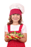 Little girl cook holding dish with salmon seafood Stock Image