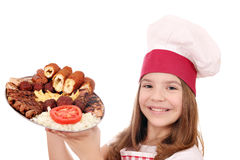 Little girl cook holding grilled meat on plate Stock Image