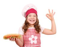 Little girl cook with hot dog and ok hand sign Royalty Free Stock Image