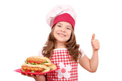 Little girl cook with hot dog and thumb up Royalty Free Stock Images