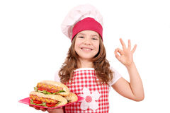Little girl cook with hot dogs and ok hand sign Royalty Free Stock Images