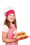 Little girl cook with hot dogs on plate Stock Photography