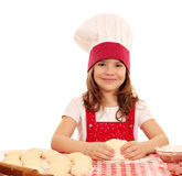 Little girl cook kneading dough Royalty Free Stock Images