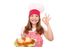 Little girl cook with lasagne and ok hand sign Stock Images