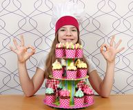 little girl cook with muffins and ok hand sings Stock Photos