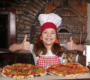 Little girl cook with pizza and thumbs up in pizzeria Royalty Free Stock Images