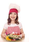 Little girl cook with prepared fish on plate Royalty Free Stock Image