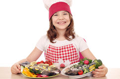 Little girl cook with prepared fishes Royalty Free Stock Photo