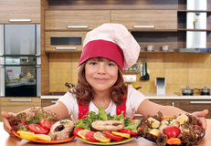 Little girl cook with prepared salmon seafood in kitch Royalty Free Stock Photo
