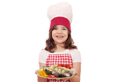 Little girl cook with prepared trout fish on dish Royalty Free Stock Images