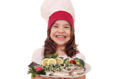 Little girl cook with prepared trout fish on plate Stock Images
