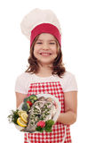 Little girl cook with prepared trouts on plate Royalty Free Stock Photos